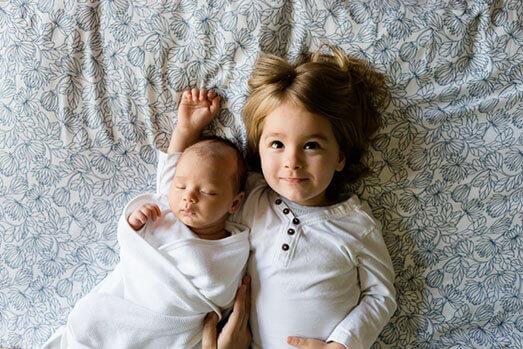 fratellini neonato e sorella sdraiati - WelFare Insieme